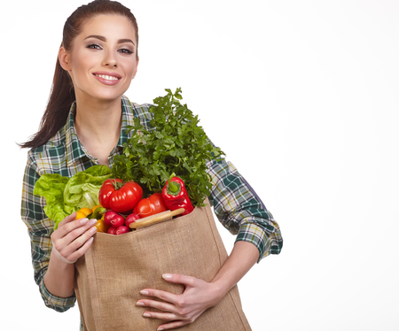 green vegetable: Isolated woman holding a shopping bag full of vegetables Stock Photo