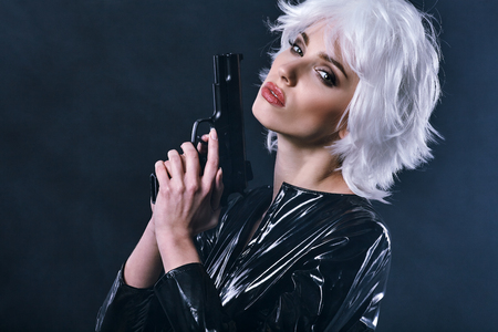 shot: beautiful sexy girl holding gun . smoke background