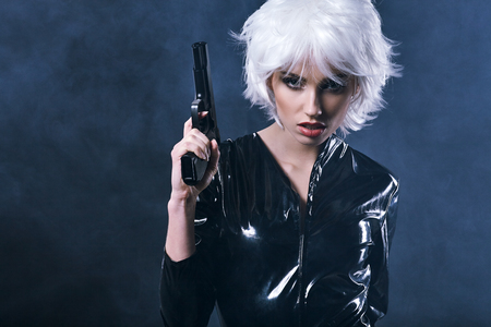 sexy young girl: beautiful sexy girl holding gun . smoke background