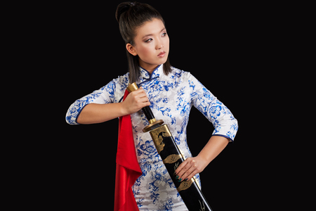 chinese dress: asian woman with japanese sword, Black background Stock Photo