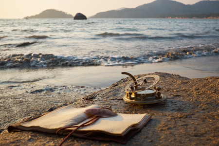 castaway: tropical rocky beach with old vintage sundial and note