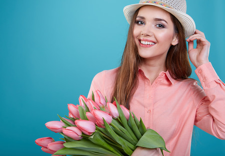 women smiling: Young beautiful woman studio portrait with tulip flowers Stock Photo