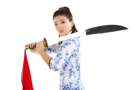 aggressively: young beautiful Japanese woman in kimono looking aggressively at camera and holding katana sword Stock Photo