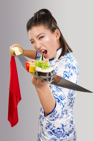 Young asian woman is holding sushi on sword Stock Photo