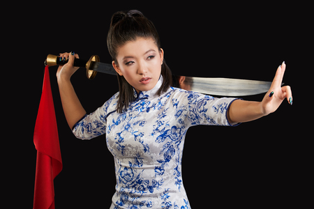aggressively: young beautiful Japanese woman looking aggressively at camera and holding sword