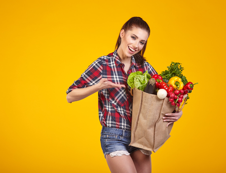 veggies: Smiling woman carrying a bag with vegetables. Yellow background. Stock Photo