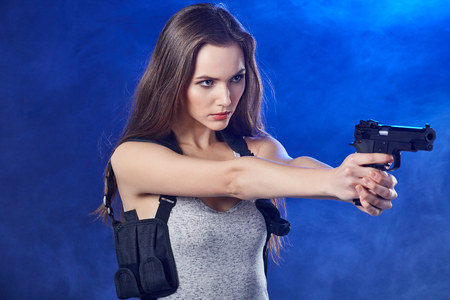 weapon: beautiful sexy girl holding gun . smoke background