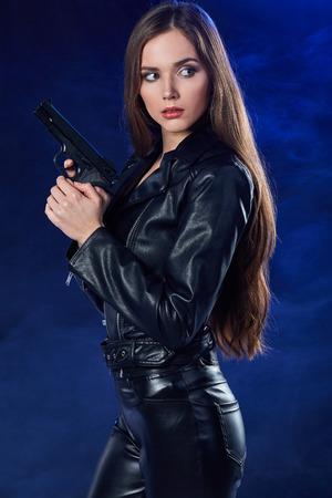 美しいセクシーな女の子ホールディング銃。煙の背景 写真素材