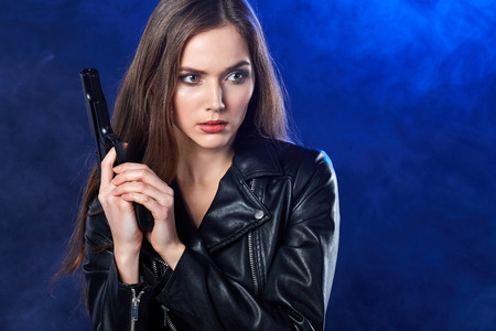 black smoke: beautiful sexy girl holding gun . smoke background