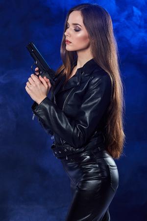 raider: beautiful sexy girl holding gun . smoke background