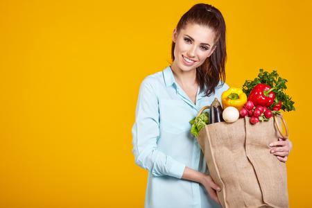 vida natural: estilo de vida saludable con la comida vegetariana verde. joven bolsa de la compra asimiento de la mujer con verduras.