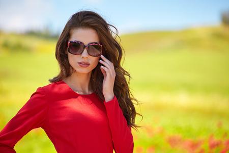 foto al aire libre de la hermosa chica sexy en elegante vestido posando en el campo de verano de amapolas rojas