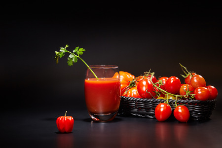 vaso de jugo: Glass of tomato juice with vegetables on black background Foto de archivo