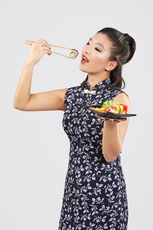 Junge schöne Sushi asiatische Frau essen mit Stäbchen