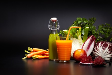 carrot: Fresh vegetable juices on black table Stock Photo