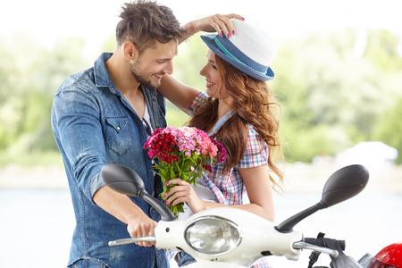 Portret van gelukkige jonge liefde paar op scooter in een park in de zomer tijd Stockfoto