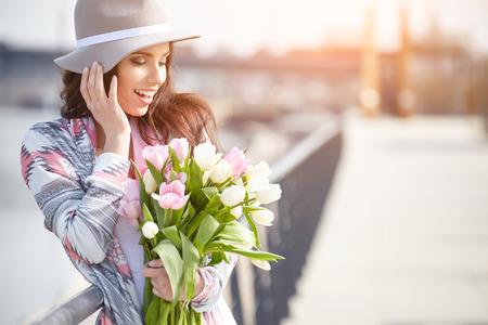 olfato: Mujer joven con un ramo de tulipanes en la calle.
