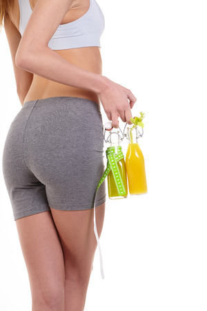 Young Woman with perfect healthy thin body with measure and juice in bottle. Weight loss and slimming concept.