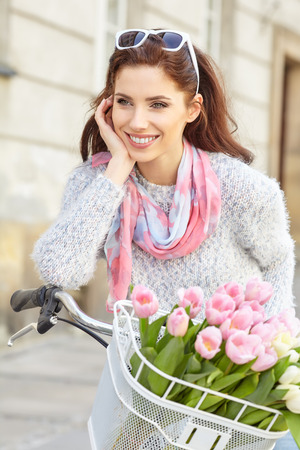 Young beautiful woman dressed in pastel on bicycle, pink and white tulips in a basket, spring outdoor. Archivio Fotografico