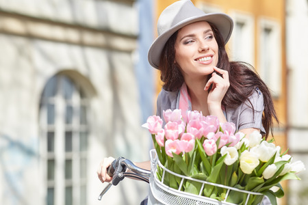 Joyful stylish woman in gray hat  on a bicycle with juice, pink pastel tulips in basket.