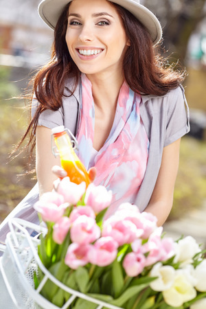 beaty: Joyful stylish woman in gray hat  on a bicycle with juice, pink pastel tulips in basket.