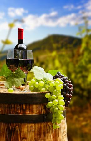 赤ワインボトルとワイングラス木造バレルに。美しいトスカーナの背景