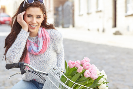 Young beautiful woman dressed in pastel on bicycle, pink and white tulips in a basket, spring outdoor. Stok Fotoğraf