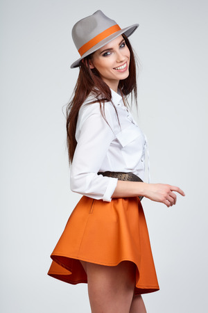 Młoda kobieta z wiosny kapelusz przed niebieskim tle