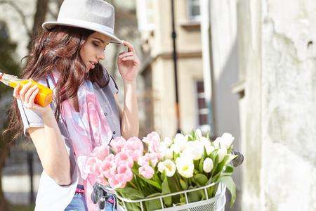 Blije modieuze vrouw in grijze hoed op een fiets met sap, roze pastel tulpen in de mand.
