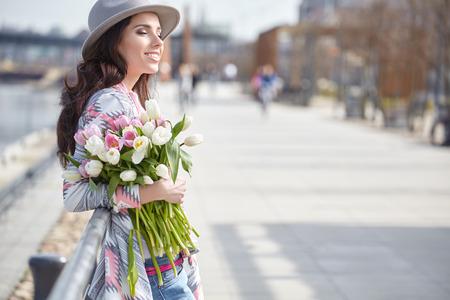 Schöne moderne junge Frau im Frühling. Frau mit Blumenstrauß der Tulpen