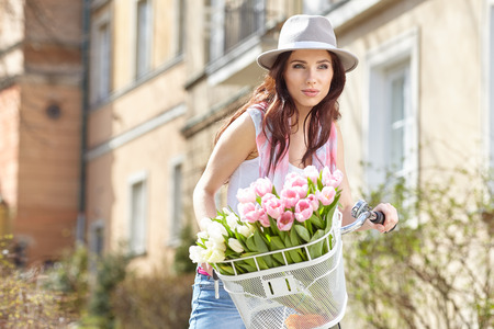 beaty: Joyful stylish woman in gray hat  on a bicycle with spring flowers on a background of the city