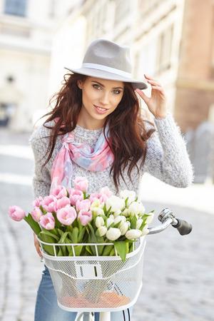 mujeres ancianas: Mujer elegante en sombrero gris en una bicicleta con flores de primavera sobre un fondo de la ciudad Foto de archivo