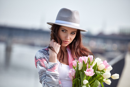 gorgeous girl: Beautiful modern young woman in springtime. Woman with bouquet of tulips