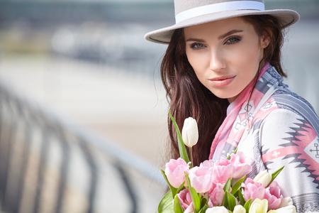 Mooie moderne jonge vrouw in de lente. Vrouw met boeket van tulpen Stockfoto