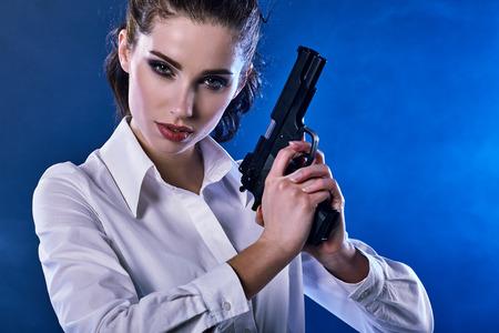 action girl: beautiful sexy girl holding gun . smoke background