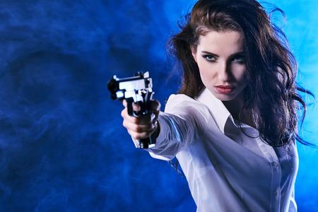 pistola de explotación de hermosas sexy girl. Fondo de humo  Foto de archivo