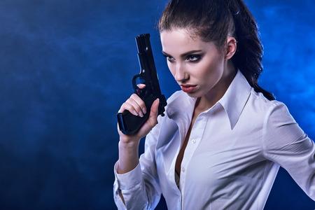 mujer con pistola: pistola de explotación de hermosas sexy girl. Fondo de humo  Foto de archivo