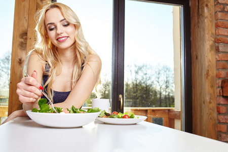 eating salad: Smiling young woman eating fresh salad in modern kitchen Stock Photo
