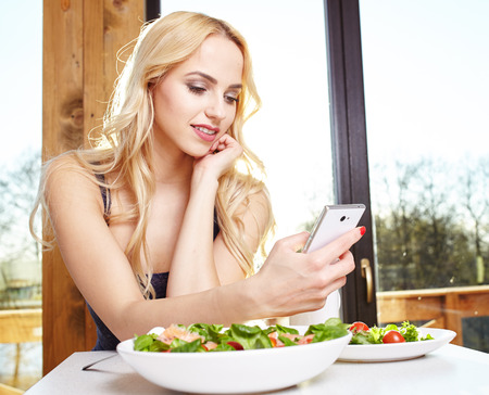 young women: Young sexy women watch her phone and have a breakfast at home in the morning