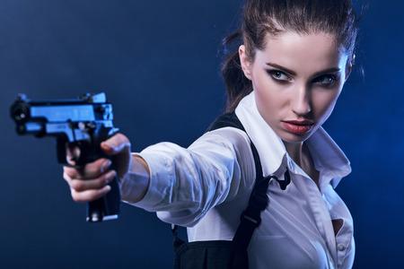 pistola: pistola de explotación de hermosas sexy girl. Fondo de humo  Foto de archivo