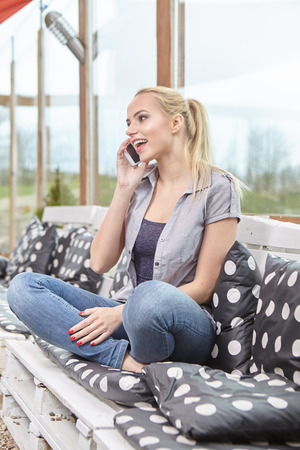 woman on phone: female enjoying recreation time while chatting with her mobile phone on terrace, smiling successful young woman read good news on the smart phone