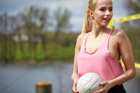 long weekend: Joyful sexy blond girl playing volleyball outdoors on the lakeside