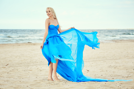 blue sea: Beautiful blonde girl in a blue dress against the sea