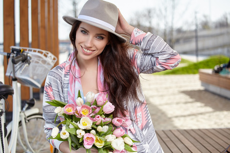 stylish woman in gray hat on a bicycle with spring flowers on a background of the city