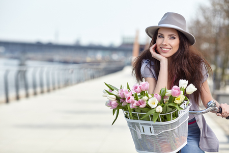 beaty: stylish woman in gray hat on a bicycle with spring flowers on a background of the city