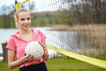 people in action: Sports games and people concept. Young woman in sportswear volleyball player in action outdoor Stock Photo
