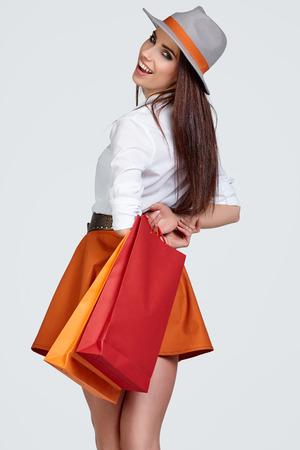 looking behind: shopping woman holding bags, looking behind. sensual female model smiling.