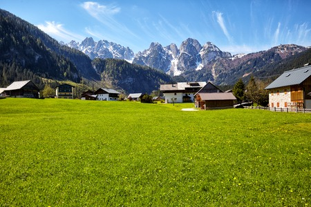 dolomite: Country road leading to the alpine houses, in the background of green meadows and high peaks of the Alps
