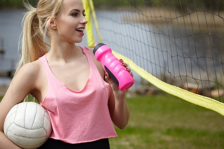 summer sport: summer vacation, sport and people concept - young woman with ball playing volleyball