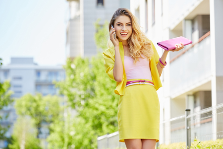 Beautiful blonde young woman wearing yellow dress walking on the street